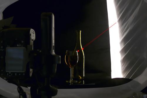 Der Aufbau für das Bild sieht so aus, dass das Lichtzelt bis auf die hintere rechte Ecke komplett abgedunkelt wurde und innen mit einem schwarzen Samt ausgekleidet wurde. Beleuchtet wird dann von außen mit einem Blitz oder eine Dauerlichtlampe durch die nicht abgedunkelte Ecke.