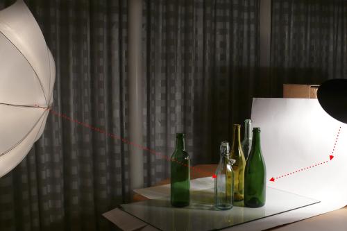 Die Flaschen werden von links vorne mit einem Blitz auf niedrigster Stufe ausgeleuchtet. Der zweite Blitz leuchtet den weißen Hintergrund mit einem Hintergrundreflektor aus und ist etwas heller eingestellt. Die Spiegelung des Durchlichtschirms konnte bei dieser Konstellation mit einem Polfilter eliminiert werden.