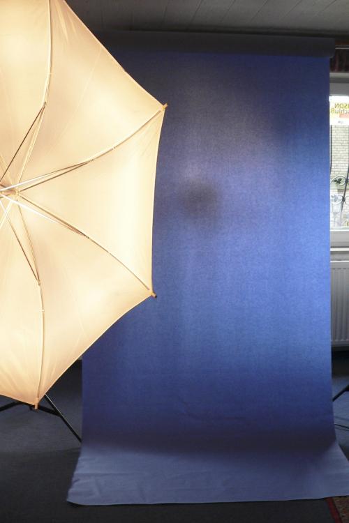 Eine Rolle mit einer hellblauen Vließtischdecke wurde hier auf einem mobilen Hintergrundgestell befestigt und dient als Hintergrund.