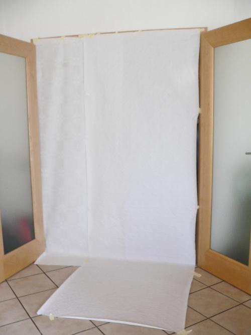 Im einfachsten Fall können Sie Papiertischdecken einfach im Türrahmen festkleben. Dann haben Sie die Möglichkeit den Hintergrund auch von hinten zu beleuchten.
